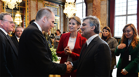 In the front of the picture, Turkish President Abdullah Gül (left) shakes hands with Jens Bjørn Andersen (right) after being introduced by Danish Prime Minister Helle Thorning-Schmidt (middle).