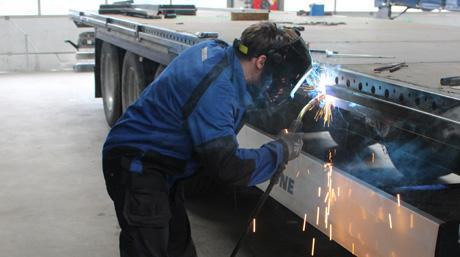 Man welding trailer