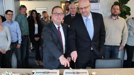 Michael Hollstein cutting office merger cake in Hamburg